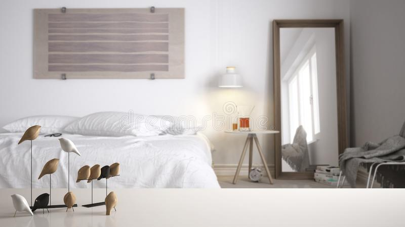 白色台式或架子与minimalistic鸟装饰品,小鸟knick -诀窍在被弄脏的当代卧室有双人床的 免版税库存图片