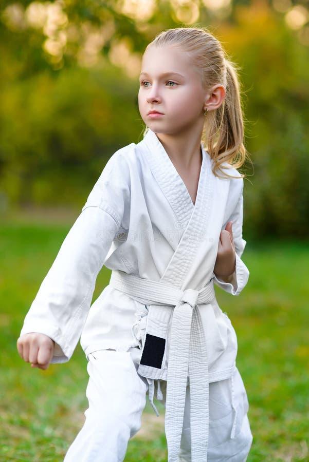 白色和服的女孩在训练空手道期间 免版税图库摄影