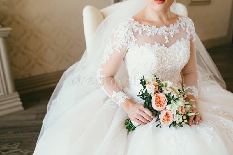 白色和橙色花华美的花束在迷人的妇女的手上一件白色礼服的 新娘坐椅子 库存照片