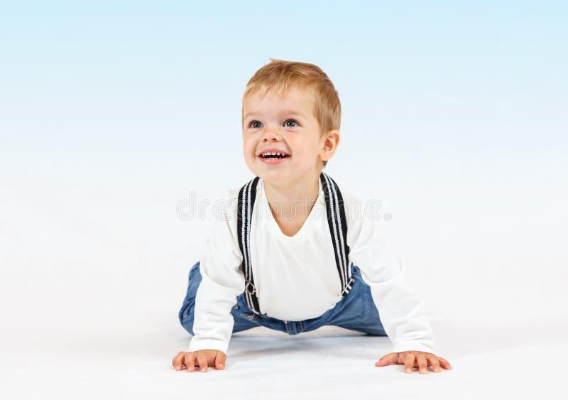 白色和浅兰的背景的愉快的小男孩 库存照片
