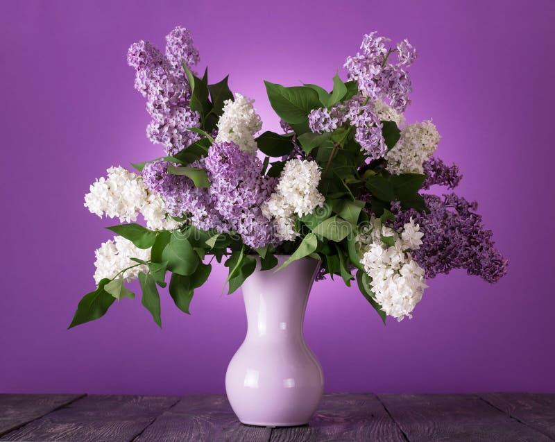 白色和淡紫色花花束在花瓶的在桌上 免版税库存照片