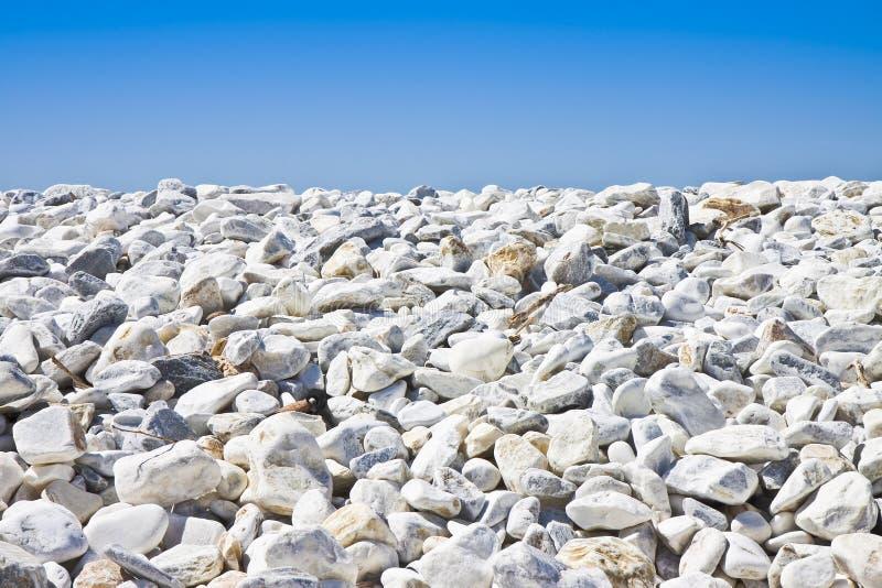 白色和灰色石头软软地被环绕反对天空蔚蓝 免版税库存图片