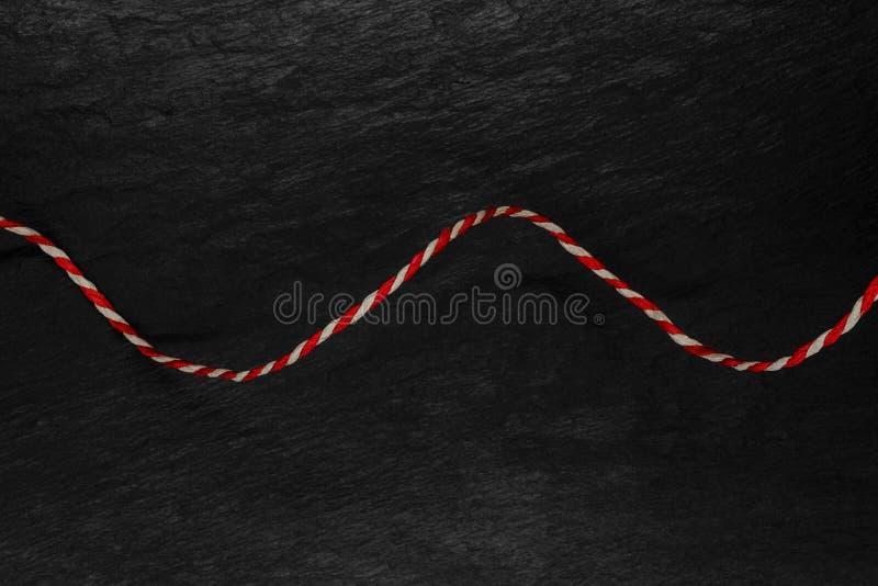 白色和红色螺纹的抽象构成黑石背景表面上的 免版税库存照片