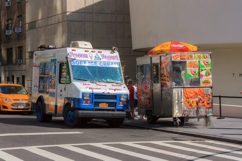白色和蓝色冰淇凌搬运车和热狗推车在一条街道上在新 免版税库存照片