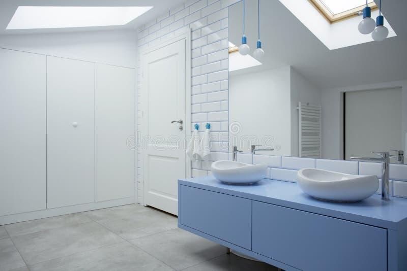 白色和蓝色卫生间内部 图库摄影