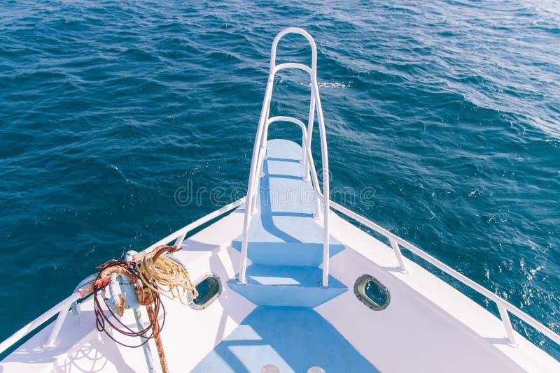 白色和蓝色小船弓和Pullpit与生锈的船锚和蓝色S 库存照片