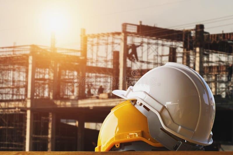 白色和黄色安全帽在建造场所 免版税库存照片