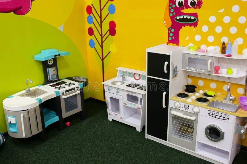 白色和黄色玩具厨房 女孩的比赛在娱乐中心或在房子里 儿童时间 减速火箭的戏剧厨房 免版税库存照片