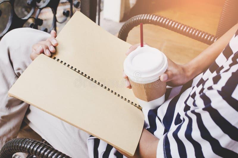 白色和黑衬衣的人,拿着咖啡坐椅子,看书,您的文本的拷贝空间 免版税图库摄影