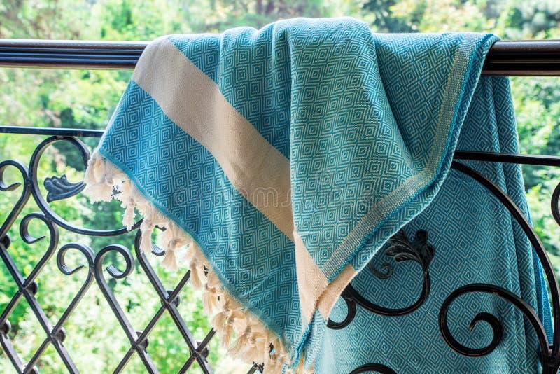 白色和绿松石土耳其在锻铁栏杆的peshtemal/毛巾与模糊的自然在背景中 库存照片