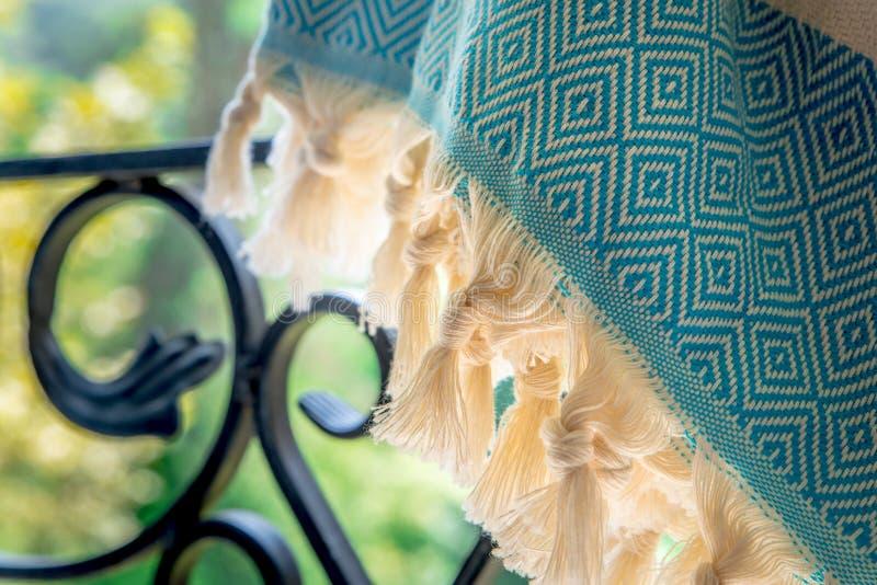 白色和绿松石土耳其在锻铁栏杆的peshtemal/毛巾与模糊的自然在背景中 库存图片