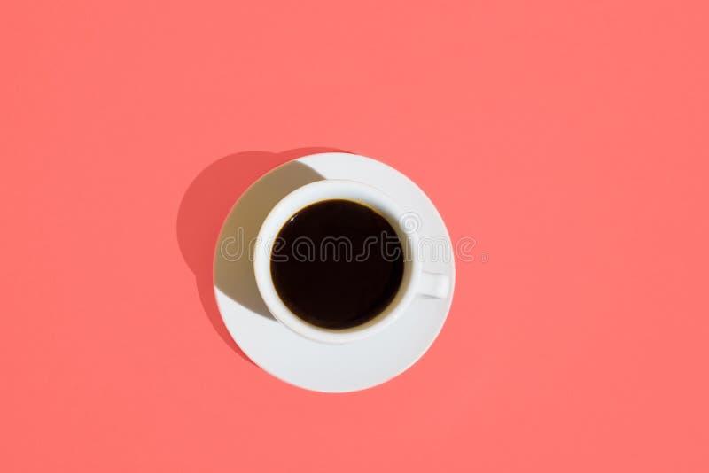白色咖啡与茶碟的在时髦生存珊瑚颜色背景 顶视图 早晨能量时尚女性企业概念 库存图片