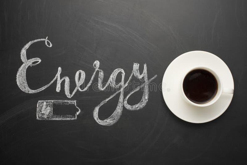 白色咖啡在黑暗的纹理的与能量和电池的题字!一个精力充沛的早晨的概念,和是 库存图片