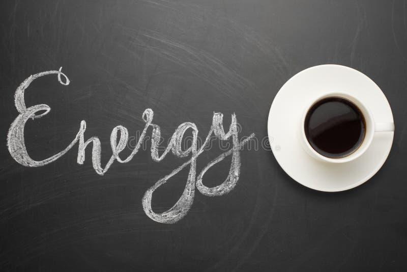 白色咖啡在黑暗的纹理的与题字能量!精力充沛的早晨的概念和天的初期 免版税图库摄影