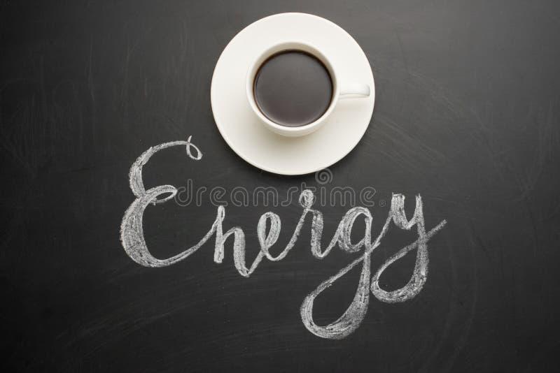 白色咖啡在黑暗的纹理的与题字能量!精力充沛的早晨的概念和天的初期 库存图片