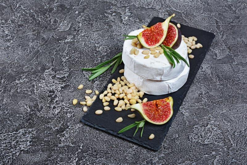 白色咸味干乳酪乳酪或软制乳酪食家开胃菜用新鲜的无花果,松果和迷迭香香料在黑板岩板 免版税库存图片