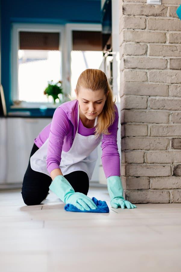 白色围裙洗涤的地板的少妇在她的膝盖 免版税库存图片