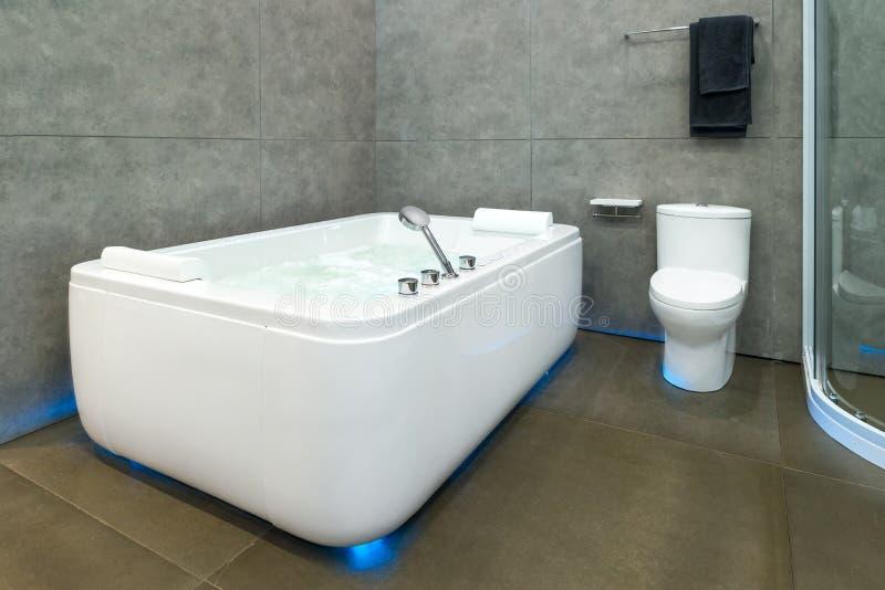 白色圆的极可意浴缸用打旋的水在旅馆温泉的卫生间里 库存图片
