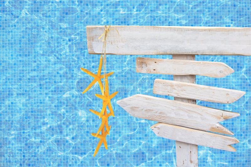 白色土气木箭头签字与在土耳其玉色马赛克水池水的黄色海星 免版税库存图片