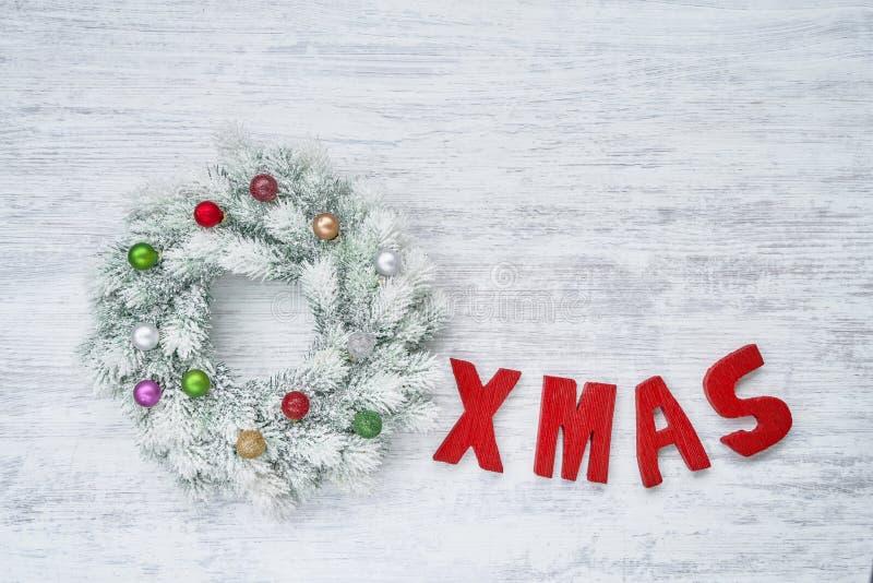 白色圣诞节快乐缠绕与在白色木的圣诞节装饰品 免版税库存图片