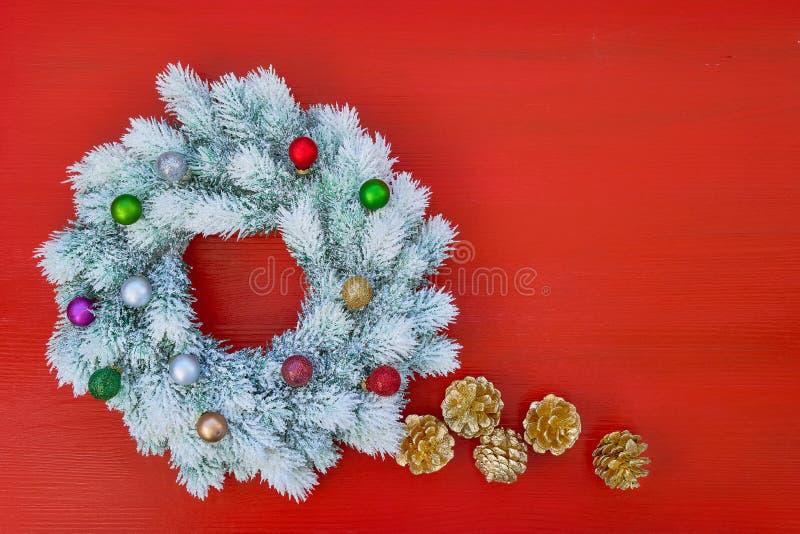 白色圣诞节快乐缠绕与在红色backgroun的圣诞节装饰品 库存照片