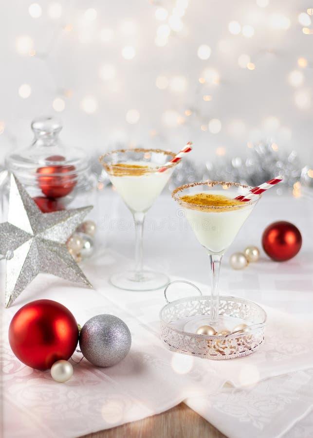 白色圣诞节快乐饮料,蛋黄乳,在与圣诞装饰的一个明亮的设置 免版税库存照片