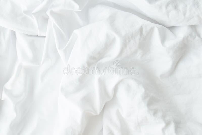 白色在夜睡眠软的焦点以后的卧室起了皱纹fabic纹理,没有整理好的床单的关闭 免版税库存照片