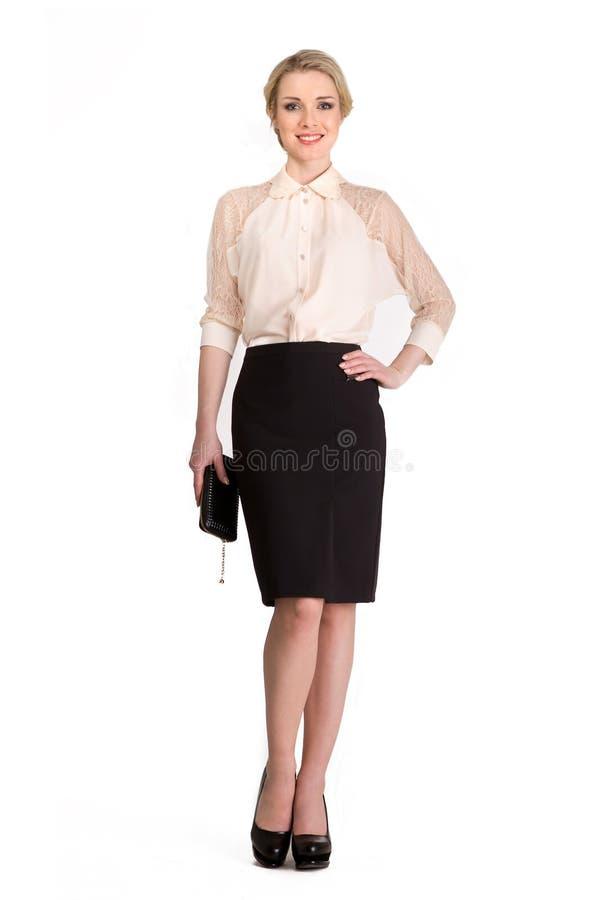 白色在白色隔绝的女衬衫和黑裙子的美丽的白肤金发的女商人 免版税库存照片