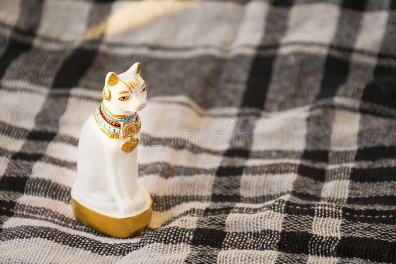 白色埃及猫雕象被检查的一揽子表面上的 传统埃及礼物元素 免版税库存图片