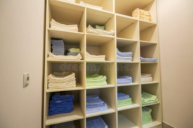 白色塑料内阁或衣物开放衣橱内部与被堆积的堆的在架子的干净的五颜六色的亚麻布 ?? 库存照片