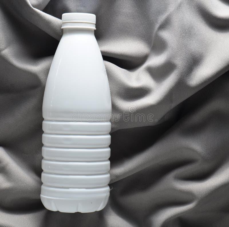 白色塑料瓶在一张灰色丝绸桌布的酸奶,顶视图 免版税库存照片
