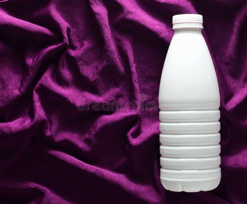 白色塑料瓶在一张红色丝绸桌布的酸奶,顶视图 免版税图库摄影