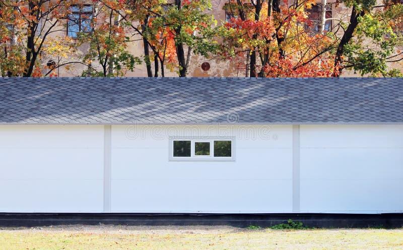 白色墙壁纹理房子,暗箱,在多彩多姿的叶子秋天森林背景的灵活的棕色瓦片  免版税图库摄影