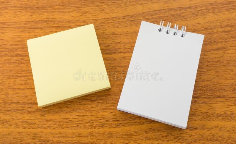 白色备忘录笔记和稠粘的柱子布朗木表面上 免版税库存图片