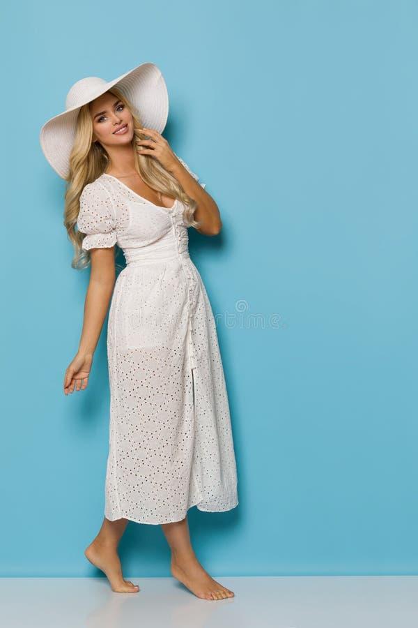 白色夏天礼服和太阳帽子的俏丽的妇女走脚尖 免版税库存照片