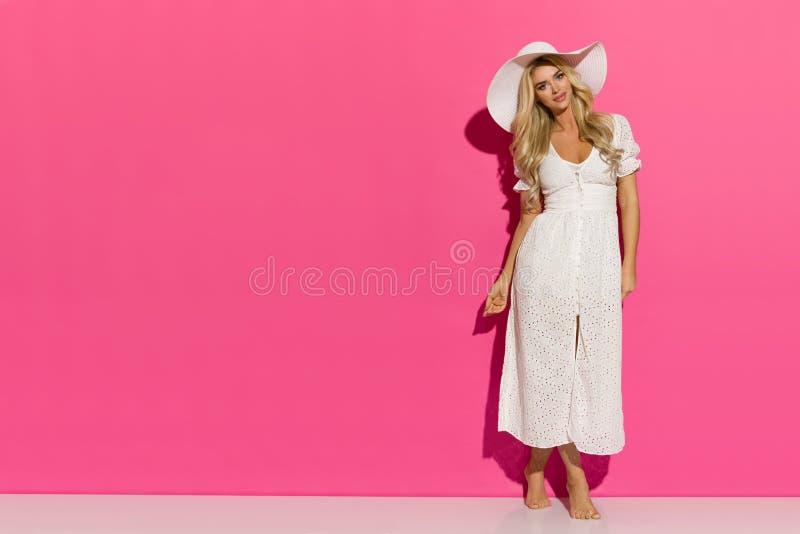 白色夏天礼服和太阳帽子的俏丽的白肤金发的妇女 免版税库存照片