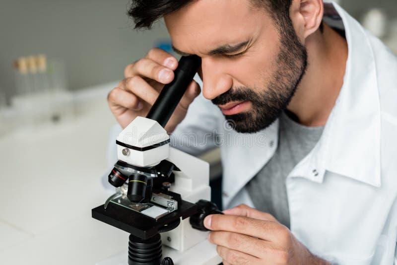 白色外套的男性科学家与显微镜一起使用在化工实验室 免版税库存照片