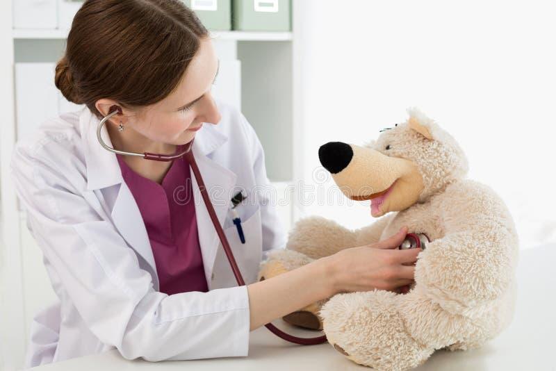 白色外套的美丽的微笑的女性医生审查玩具熊 库存照片