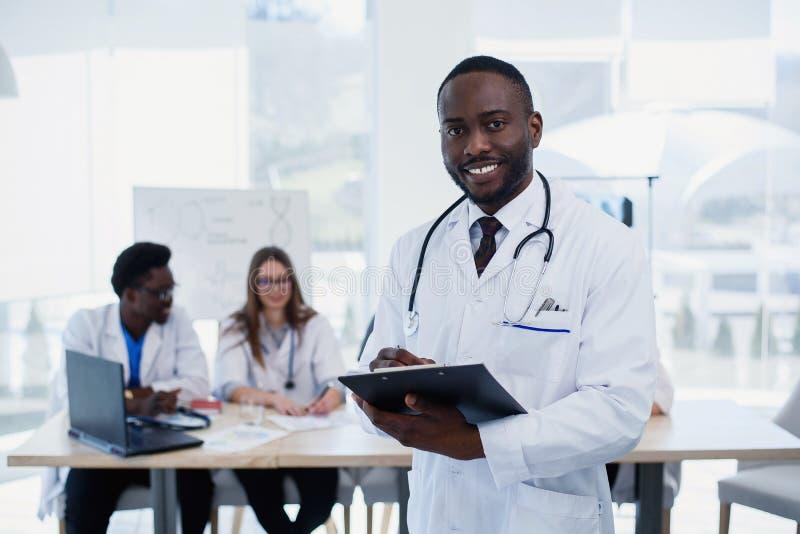 白色外套的英俊的美国黑人的医生看照相机和微笑 有听诊器的年轻医科学生 免版税库存图片