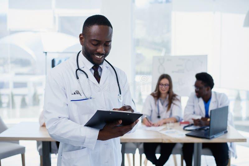 白色外套的英俊的美国黑人的医生看照相机和微笑 有听诊器的年轻医科学生 库存照片