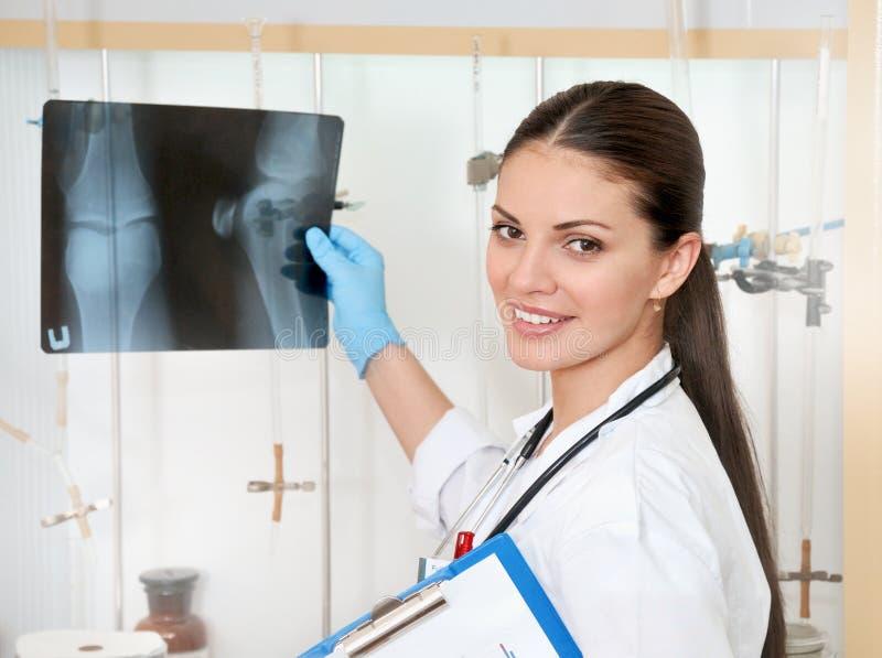 白色外套的逗人喜爱的美丽的女性医生有伦的在手上 免版税库存照片