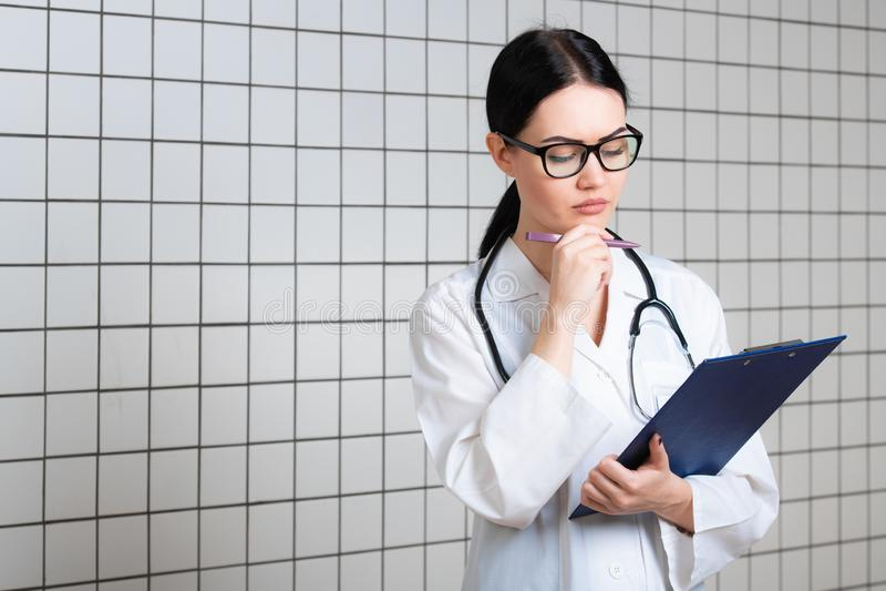 白色外科外套的年轻美丽的女性医生有黑听诊器和蓝纸持有人的在站立在的手上 免版税库存图片
