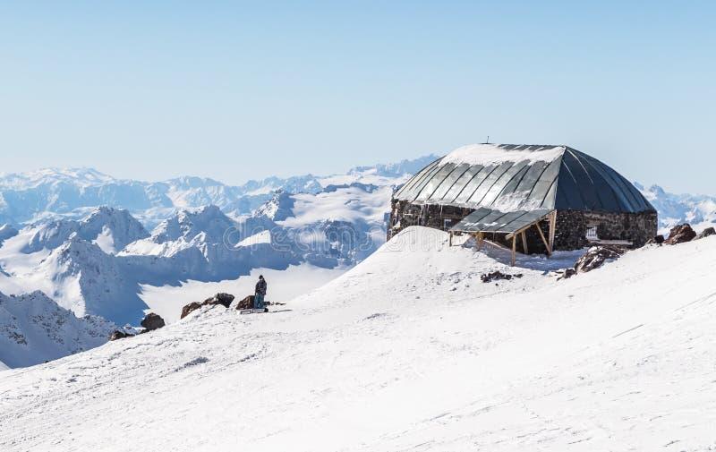 白色多雪的冬天高加索山脉在好日子 从滑雪倾斜厄尔布鲁士山,俄罗斯的全景视图 免版税库存图片