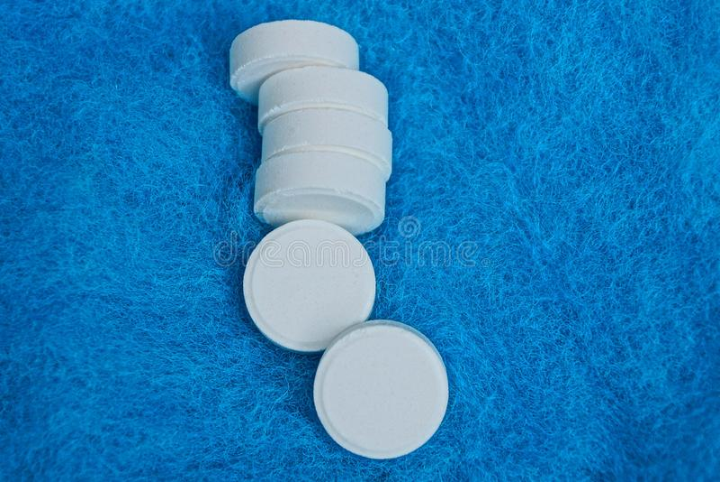 白色大圆的药片行在蓝色羊毛布料背景的 免版税库存照片