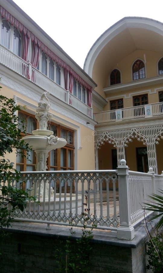 白色大理石喷泉在房子附近的 免版税库存图片