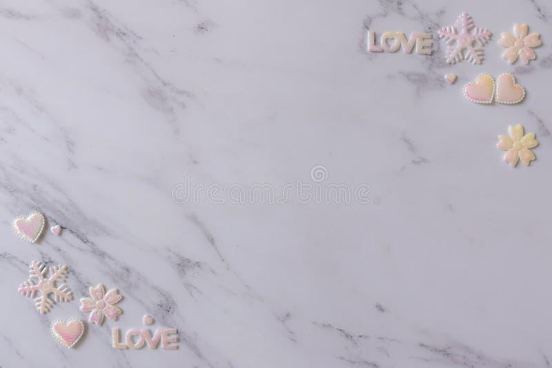 白色大理石背景平的位置用发光心脏桃红色白色爱珍珠,信件,雪花和花装饰 图库摄影