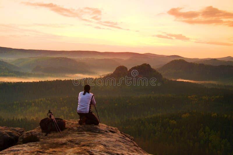 白色夹克的专业摄影师拍与照相机的照片在岩石峰顶的三脚架 梦想的老保守风景,反弹桔子 免版税库存照片