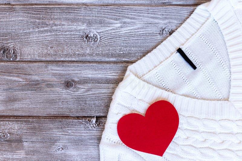 白色女性毛线衣,有红心的套头衫对此在与拷贝空间,平的位置的葡萄酒木背景 库存照片