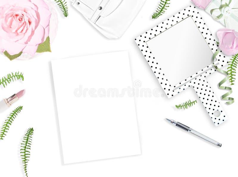 白色女性背景 平的位置 笔记本,笔,桃红色玫瑰,镜子,叶子,礼物,袋子 安置文本 每天快乐的头脑 免版税库存图片