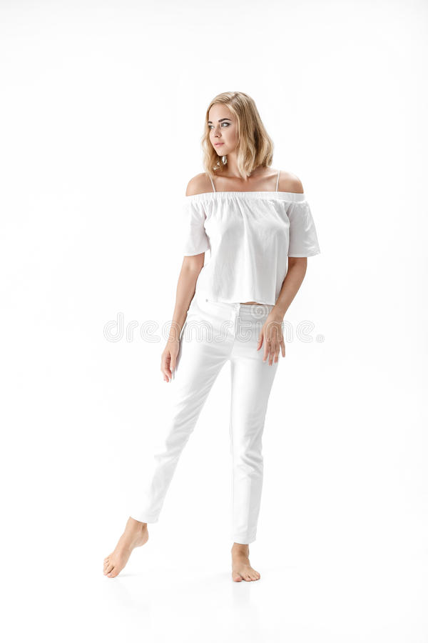 白色女衬衫和裤子的美丽的微笑的白肤金发的妇女在白色背景 库存图片